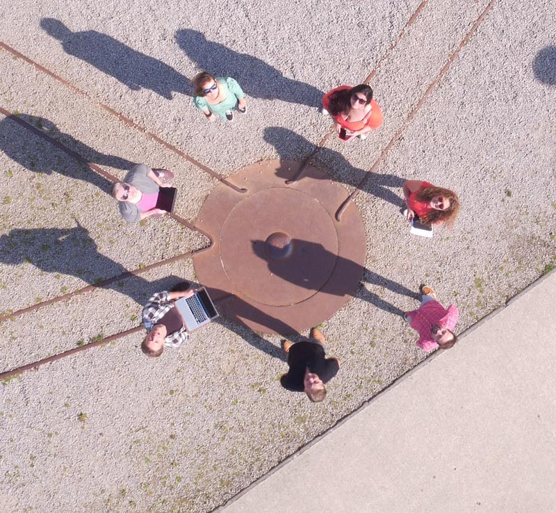 7 men and woman stood in a circle looking up towards the camera above them. Some are holding laptops and devices.