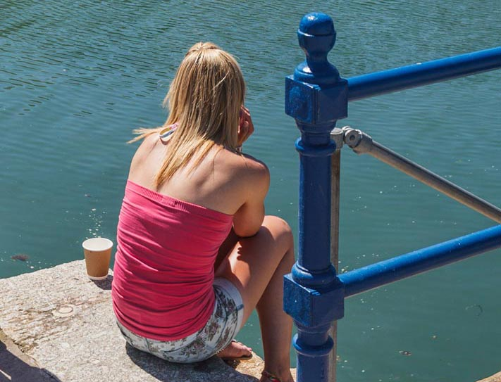 Barefoot woman, deep in thought sat on steps by the harbour drinking coffee