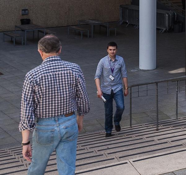 Two men wearing denim passing on steps outside