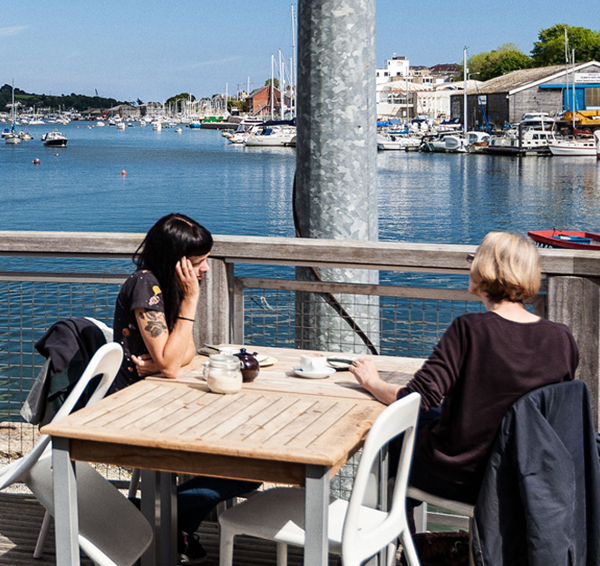 Two woman having tea and coffee at an outside table near a harbour