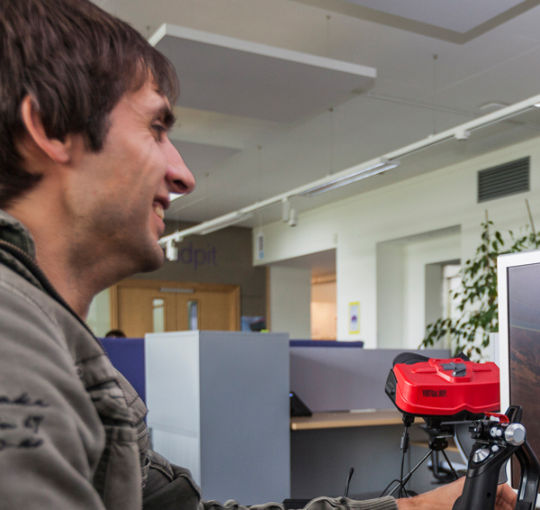 Smiling man dressed casually playing a flight simulator game on a PC in a shared office space